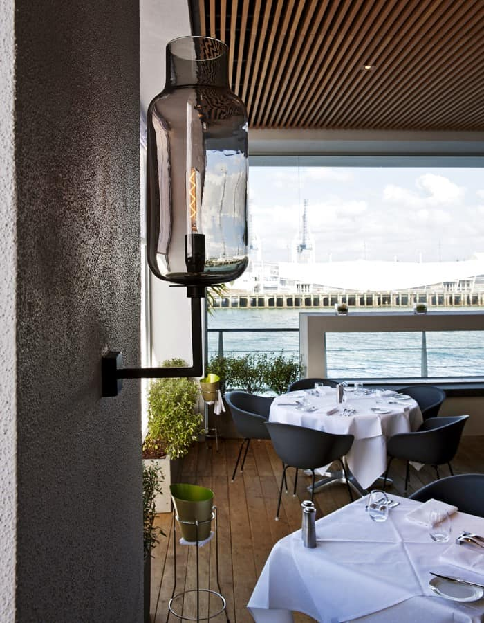 Fish restaurant in Auckland outdoor dining area with tables, chairs and glass light fitting