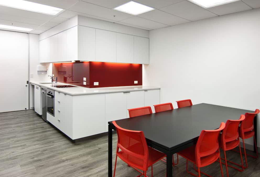 BNP Paribas in Wellington office workplace kitchen design with white walls and red features such as chairs and splashback