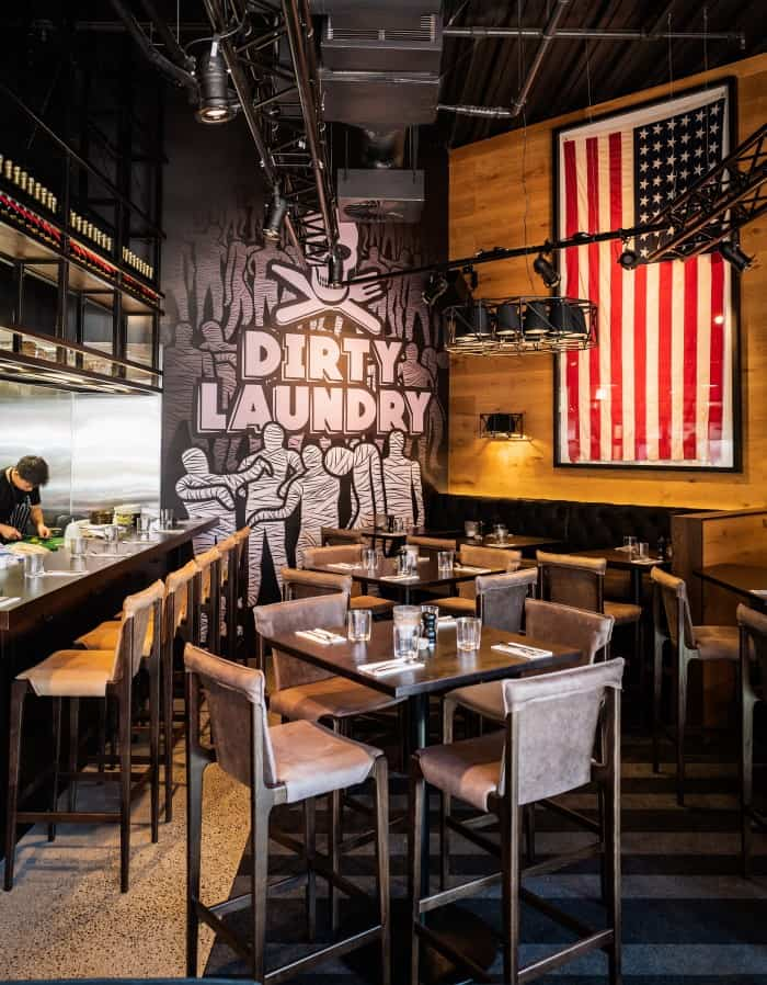 Dirty Laundry restaurant and bar in Auckland dining room design with American flag hanging on wall, and staff in kitchen