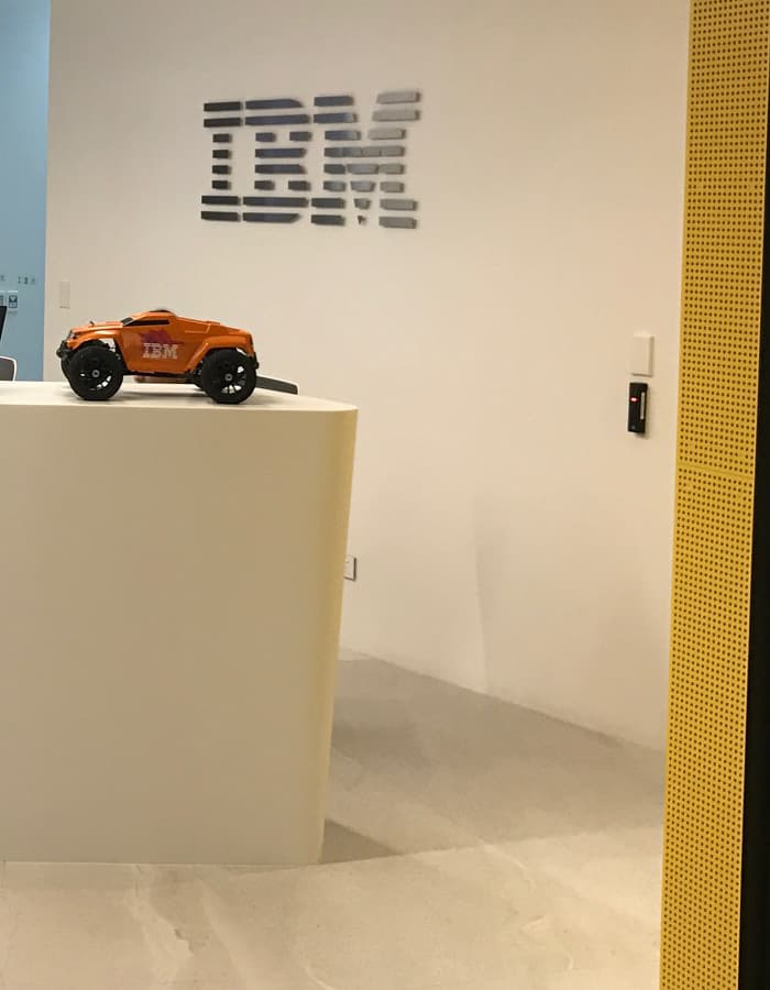 IBM office in Auckland workplace reception design with yellow wall, front desk, company signage and model car decor