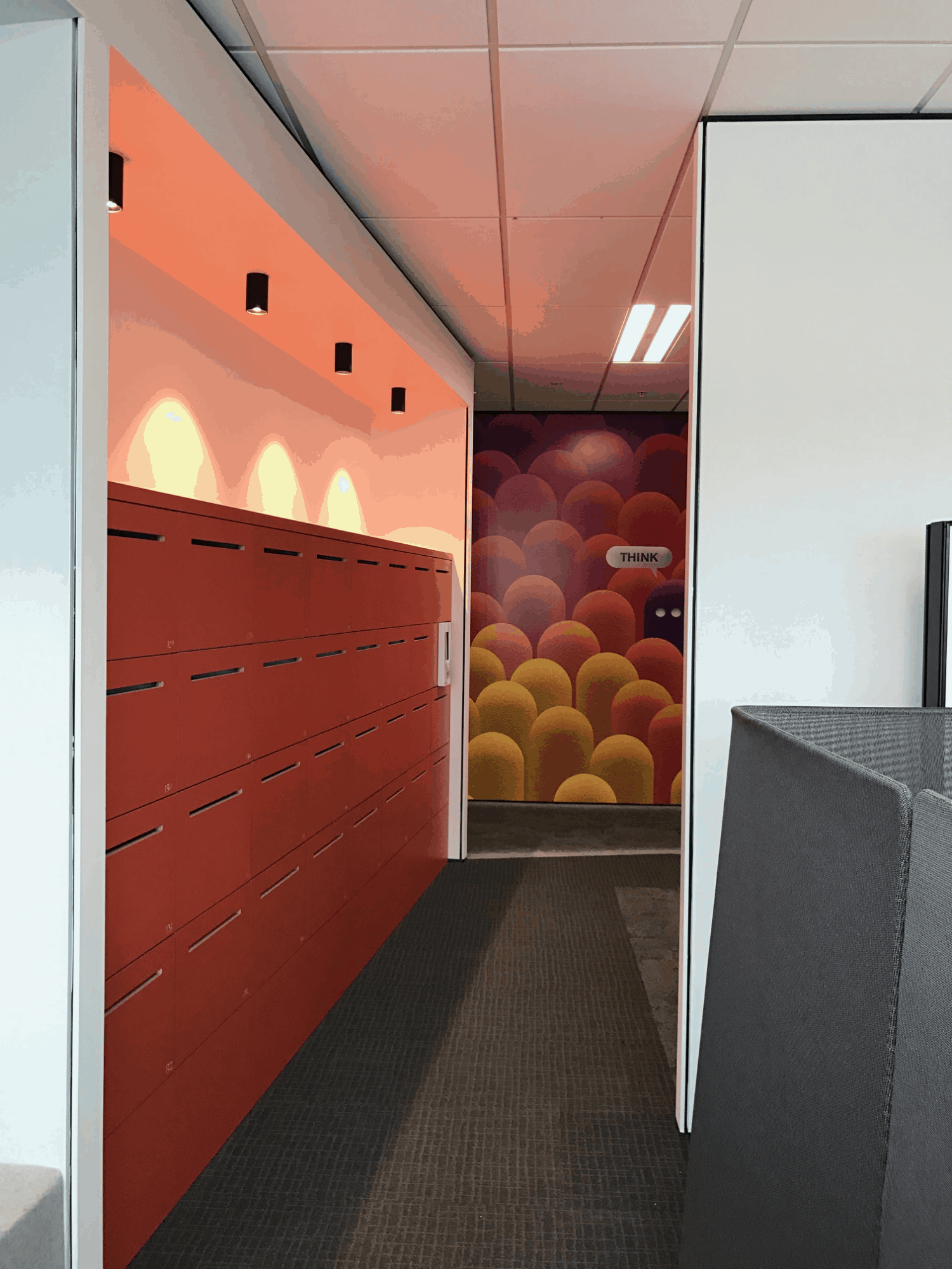 IBM office in Auckland workplace hallway design with art on back wall and red storage cubes