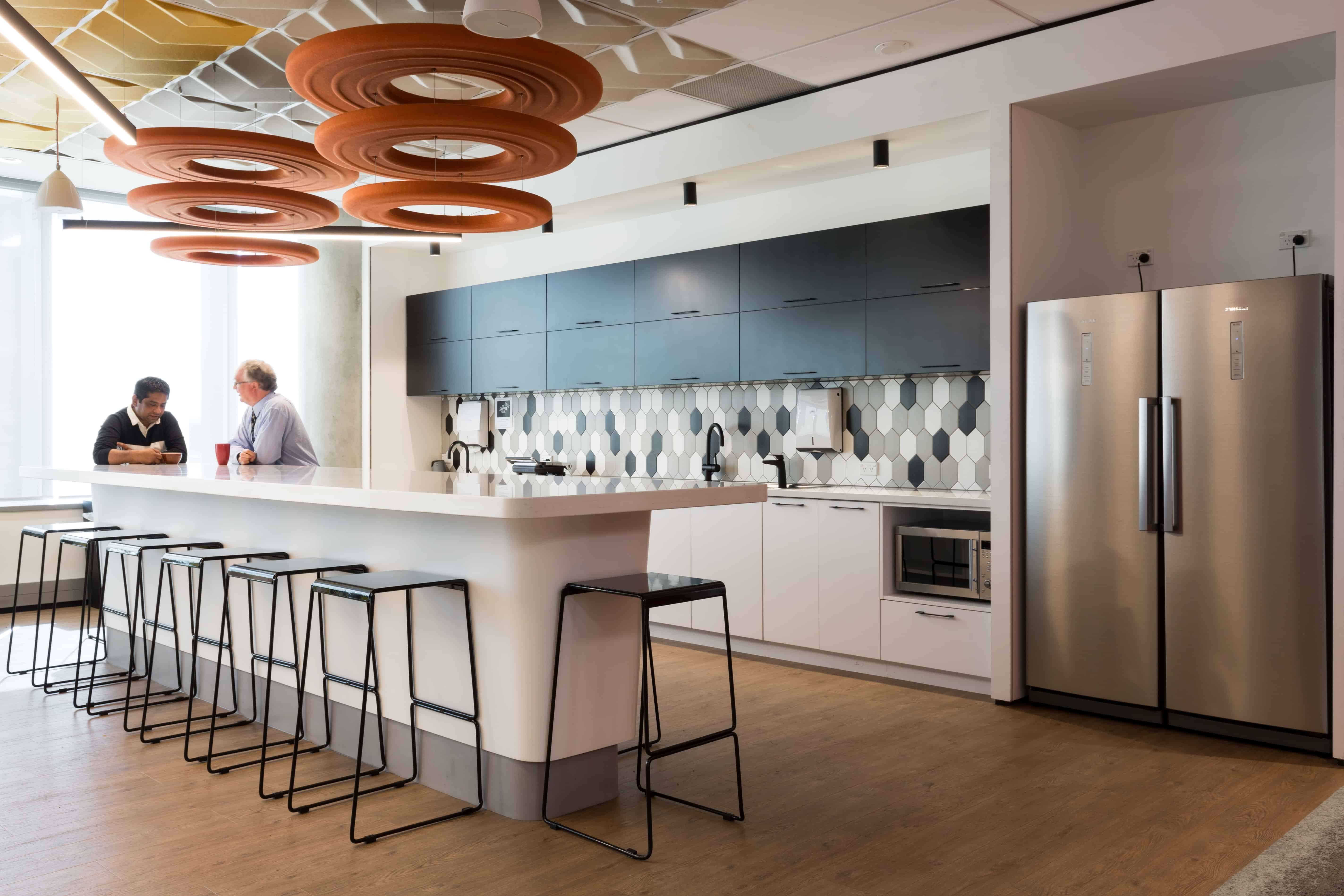 IBM office in Auckland workplace kitchen with people talking and red spiral art hanging from ceiling