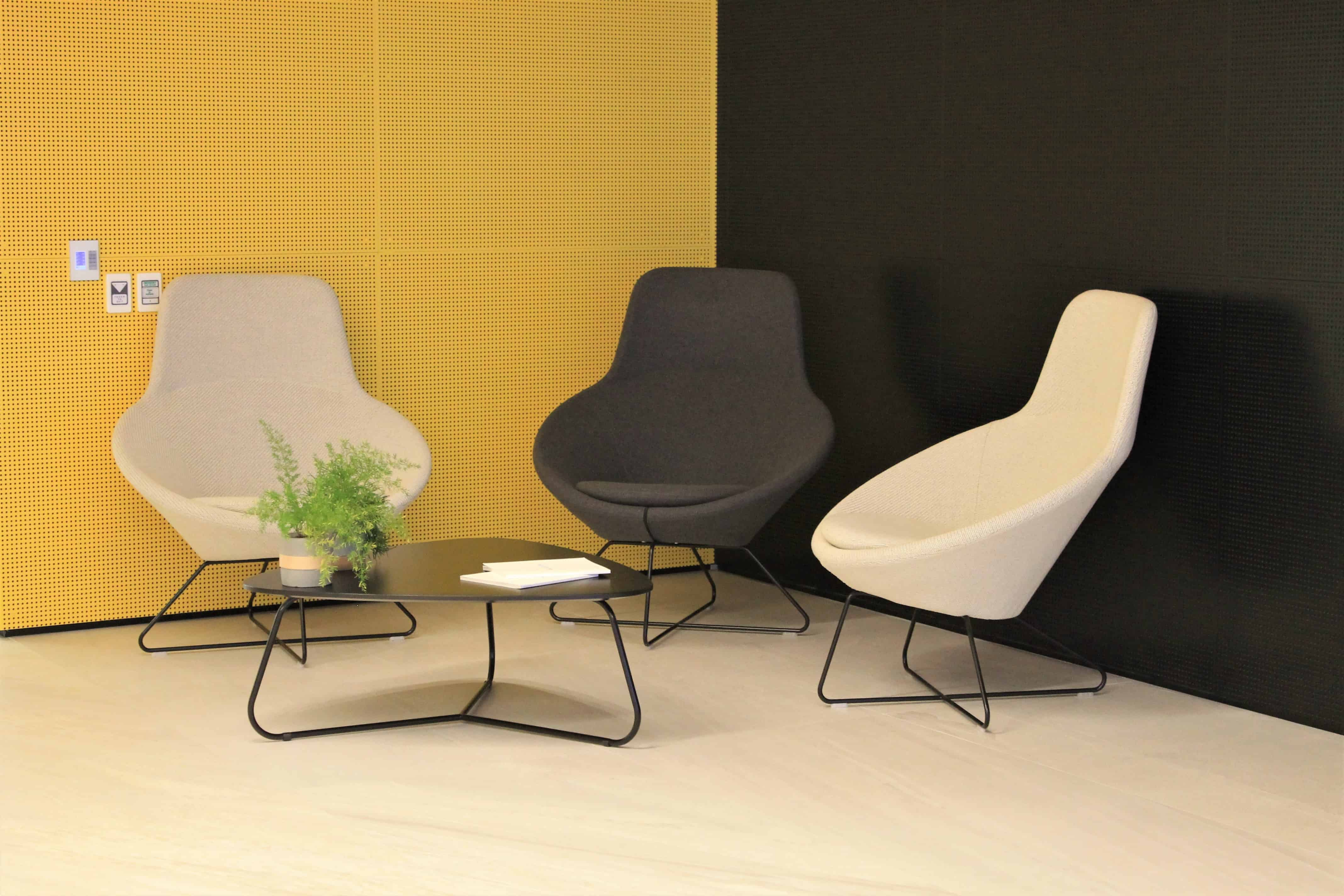 IBM office in Auckland workplace waiting area design with yellow wall and low table and chairs